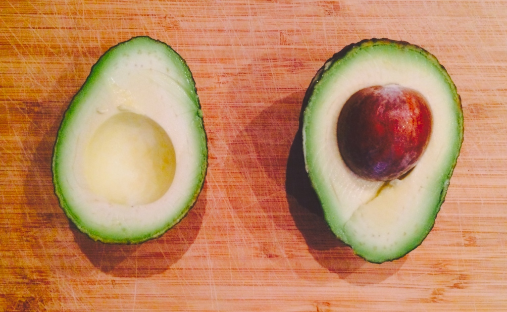 Avocado halves on wood